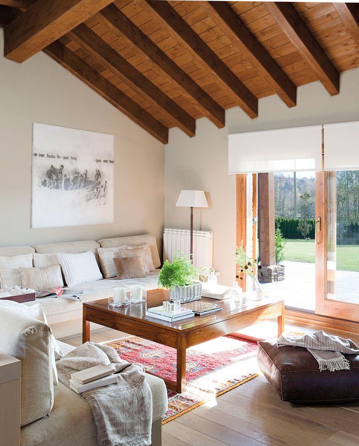00306953. Salón con vigas de madera y dos sofás beige frente al ventanal al jardín_00306953
