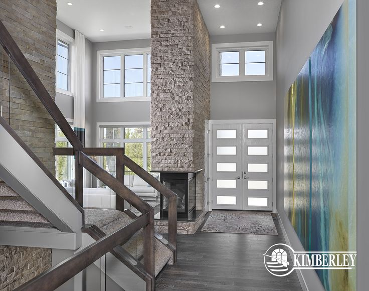 Two-storey stone, three sided fireplace is the feature of this modern foyer | Custom home by Kimberley Homes  #interiordesign #newhomedesign #homedesign #newhome #customhome #yegre #buildwithkimberley #kimberleyhomes #fireplace #greatroom #livingroom #bonusroom #stonewall #accentwall #foyer #opentoabovefoyer