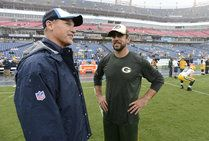 Tennessee Titans head coach Ken Whisenhunt, left, talks with Green Bay Packers quarterback Aaron Rodgers in the rain as the teams warm up. - Image credit: Associated Press