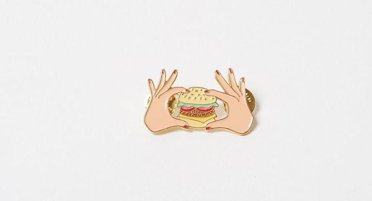 CouCou Suzette Burger Pin. Double backed burger enamel badge. Shiny gold brass. Cloisonne enamels. Butterfly hook backing. 4 x 3 cm. Exclusive to Lazy Oaf in th