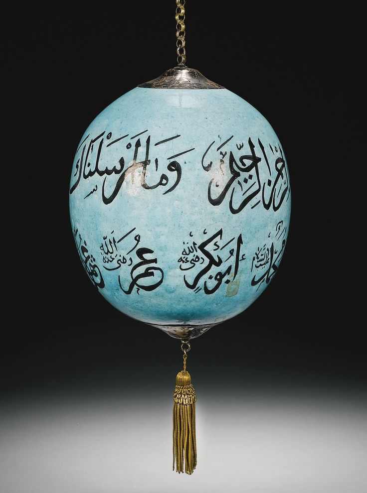 A KÜTAHYA CALLIGRAPHIC POTTERY HANGING ORNAMENT, TURKEY, 19TH CENTURY of large ovoid form, decorated in black under a turquoise glaze with calligraphic inscriptions, set at the top and bottom with two brass mounts, the top one with a long chain for hanging, the other with a golden tassle, both stamped with [possibly] tughra of Abdülmecid (r.1839-61) 18.5cm. max. diam. 83cm. with chain and tassle