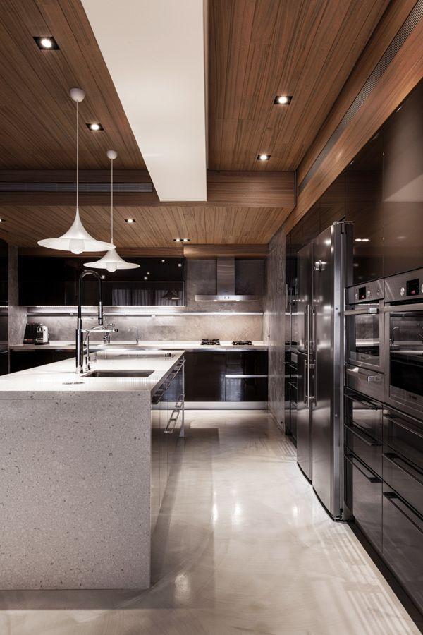 Cozinha espaçosa e moderna com a utilização de madeira escura com armários pretos. Sua ilha em tonalidade clara e seus pendentes conferem uma leveza e charme ao ambiente.
