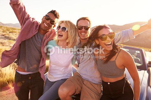 Foto de stock : Amigos en viaje por carretera sentado en carcasa de coche descapotable