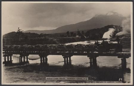 Queensland Sugar Cane Train Babinda Creek postcard Queensland picture postcard (R. Alston, Cairns real photo no.59) showinga steam train fully laden with sugar cane on the bridge crossing Babinda Creek of North Queensland, used under cover