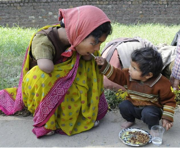 Two year old daughter feeding her double-amputee mother