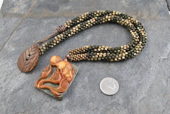 Succor Creek Jasper Hand Carved Squirrel Pendant Bead Necklace with Kumihimo Bead Strand #necklace #kumihimonecklace #pendant #pendantbead #pendantbeadnecklace #artisan #artisannecklace #handmade #handmadenecklace #woven #knotted #handwoven #handknotted #handcarved #squirrel #squirrelpendant #jasper #succorcreek #succorcreekjasper #oneofakind #miyuki #miyukiseedbeads #picasso #metallic #matte #cube #cubebeads #moss #khaki #gold #bronze #japanese #japaneseweaving