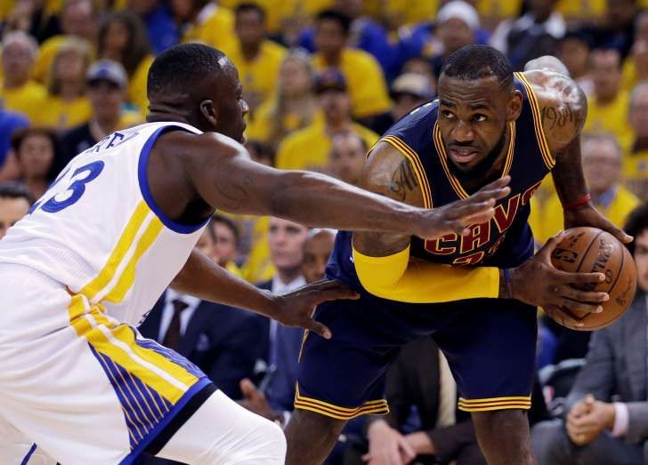LeBron James, Draymond Green: FILE - In this June 14, 2015, file photo, Cleveland Cavaliers forward LeBron James, right, is guarded by Golden State Warriors forward Draymond Green during the first half of Game 5 of basketball's NBA Finals in Oakland, Calif. A person with knowledge of the decision tells The Associated Press that James will not exercise a $21.6 million option on his contract, making him a free agent on July 1.