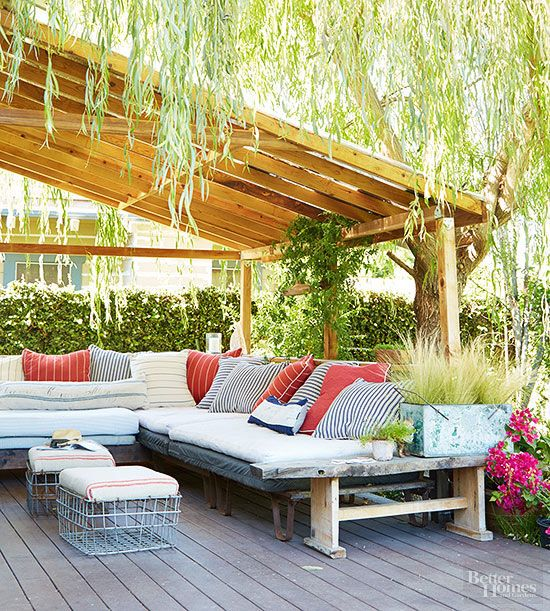 An oversized, cushioned bench offers a comfy sofalike spot to sit with guests and enjoy the outdoors. Lots of throw pillows featuring a mix of patterns and bright colors add to the comfort and style. A pergola built off the house gives welcome shade on hot summer days./