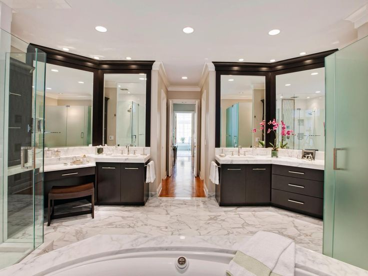White marble ties together several components in this spacious bathroom: countertops, floor and bathtub surround. The rich wood double vanities are sleek and unfussy, topped with frameless mirrors and recessed lighting for an updated, sleek look.