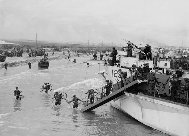 Troops of the Nova Scotia Highlanders and the Highland Light Infantry of Canada landing at Bernières-sur-Mer, 6 June 1944. Disembarking from L.C.I. of the Canadian Landing Craft Infantry (Large) Flotilla, of either the 260th, 262nd, or 264th.