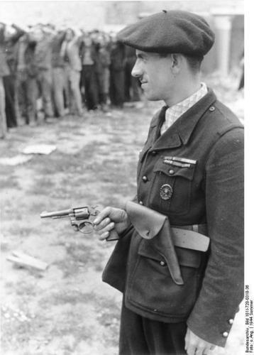 French militiaman guarding captured members of the resistance movement. France, June 21, 1944. / Un traître à son propre peuple (revolver Anglais et badge Allemand) garde des prisonniers de la résistance, 21 juin 1944: