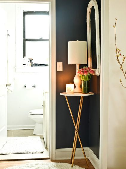 Dress up a small corner with a petite table, multi level lighting, a mirror and flowers.