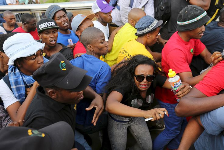 A student reacts during a confrontation with security guards as they protest over planned increases in tuition fees outside the University of Johannesburg