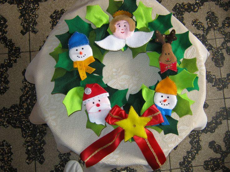Una corona navideña interesante toda hecha en paño lency de diversos tonos verdes y decorada con lindos hombrecitos de nieve...