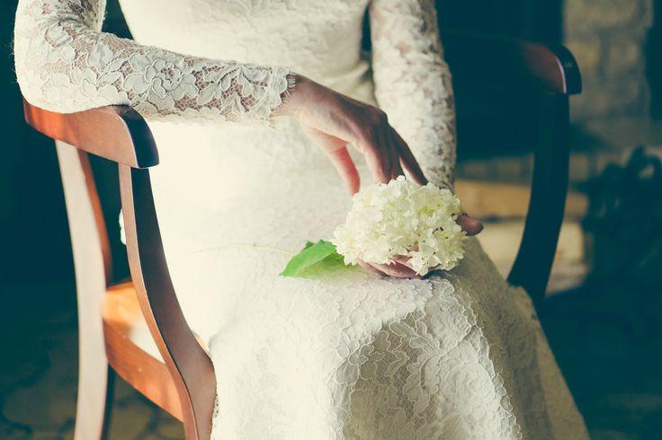 Невеста в кружевном платье с цветами в руках