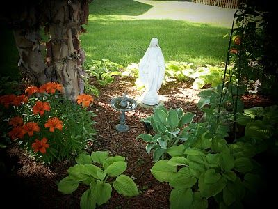 "An outdoor Mary garden statue surrounded by Lilies and Hostas. Hostas are also known as ""Assumption Lilies."""