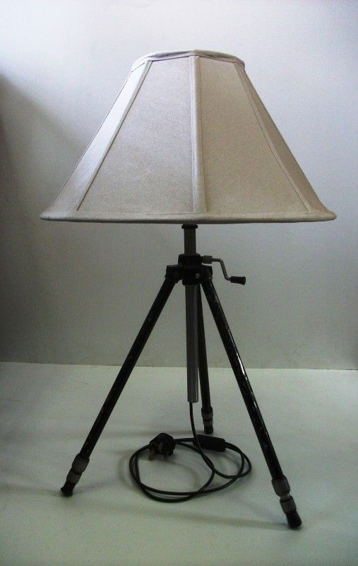 An industrial vintage style table lamp created from a discarded old metal camera tripod. With a quirky handle to adjust the timeless linen lampshade to your preferred height