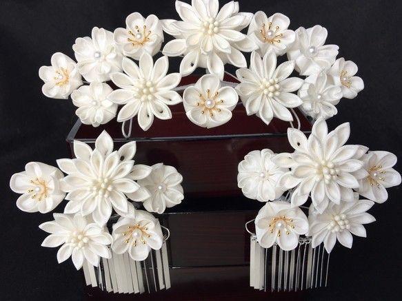 つまみ細工の、勝山簪・銀ビラ付き横挿し簪2点の3点セットです。生地は正絹の羽二重を使用しております。 花結月のオリジナル作品です。白無垢に合わせて頂ける作品です。花芯には樹脂パール・ペップ・座金を使っています。二段重ねの菊と梅 桜を華やかに飾りました。横挿しは、撮影時にどの角度からもお嫁様のお顔が良く見えるように、銀ビラにしました。キラキラと光る銀ビラが、お顔を華やかに飾ります。名前は「花嫁かんざし」です。サイズ前挿し簪~お花の部分 約横17cm 縦8cm簪足の部分長さ 11.5cm横挿し~お花の部分 約横8cm  縦7cm 銀ビラ部分  横5.5cm 縦3.5cm(15枚) 簪の部分長さ 11.5㎝純白のお花が華やかで豪華な簪のセットです。白無垢は勿論、赤や黒などお色のある打掛にも映え、美しく豪華な花嫁衣装に相応しい簪です。別途下がりをお作りする事も出来ます。下がり1本…