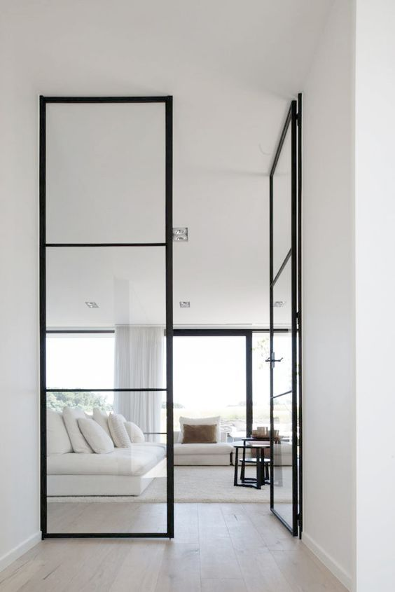 floor to ceiling black framed glass doors lead from hall to living room