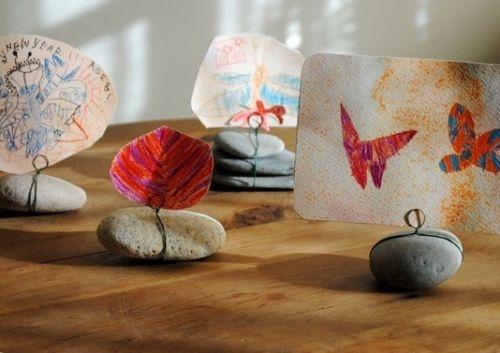 Камни-держатели – отличный вариант для хранения фотографий, детских рисунков, записок и других мелочей. Окручиваем вокруг увесистой гальки проволоку, формируем из неё петельку – и вставляем любые бумажные сокровища.