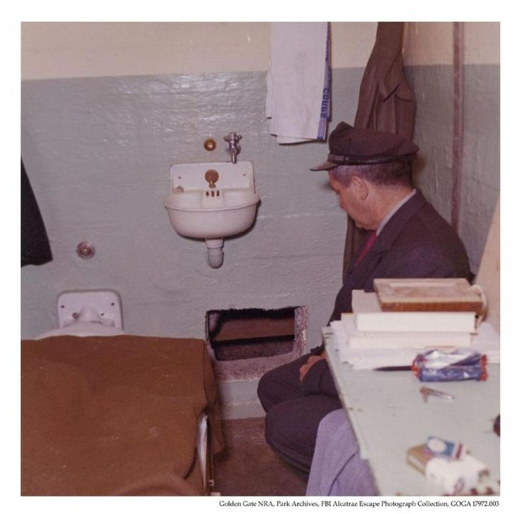 Federal Senior Correctional Officer Walron sitting in Frank Lee Morris's prison cell (#138) on cell block B, after the 1962 escape from Alcatraz Island Federal Penitentiary