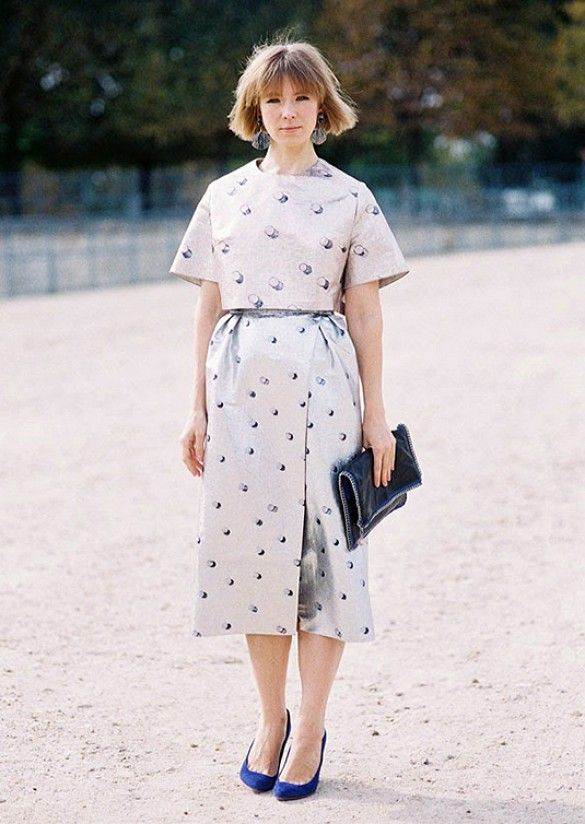 A printed midi dress is worn with a black clutch, statement earrings, and blue heels
