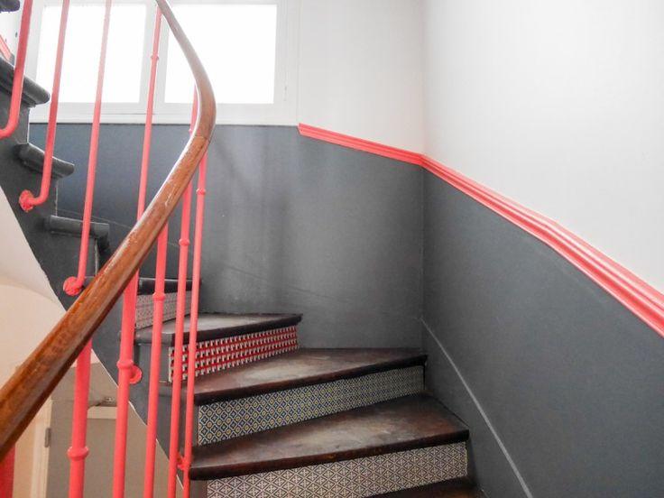 Rose fluo et gris sur les murs ; marches décorées de papier peint à motifs.