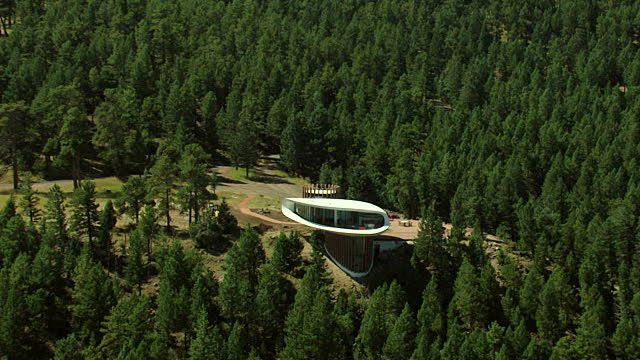 View of sleeper house by architect charles deaton and tree filled mountain surrounding elliptical curved house / Denver, Colorado, United States