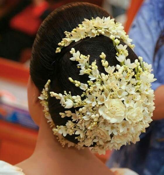 What a beautiful large low bun with real flower covering! Care however should be taken before adopting such hairstyles, as due to it's high static charge, it will cause phlegm to move up in the throat, causing the voice to quaver & a frequent urge to clear the throat. A heavy chabi chhalla with a long & wide hook if inserted at the edge of the pleats of the saree, will reduce this problem as it's hook will activate the acupressure points that act to keep the throat clear.