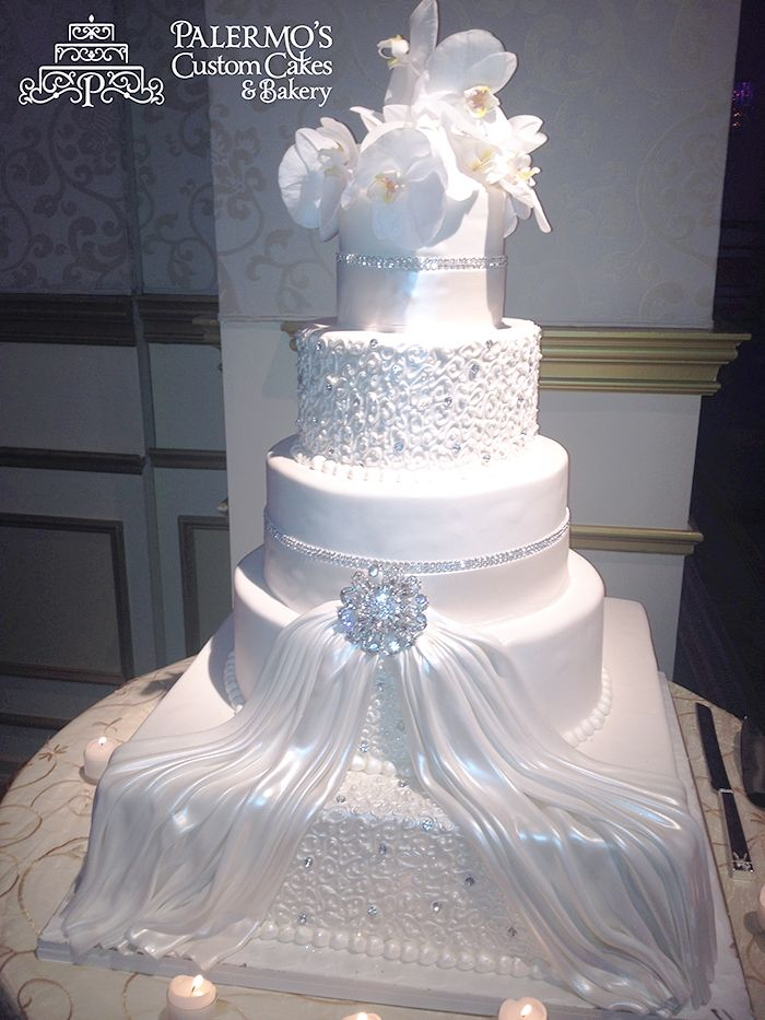 Piped Lace and Jewelry - Our bride sat with Joanne for her wedding cake with a photo of her dress. Joanne drew inspiration from her dress to create a beautiful five tier fondant wedding cake. The lace embellishments were piped by hand and overlaid with a white fondant sash to look like the front of the dress.