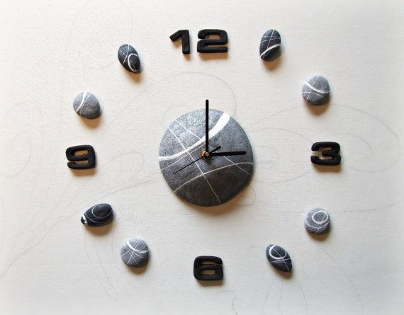 Large wall clock with river stones made of papier-mache.  Each stone represents one hour of the day and can be applied anywhere on the wall with an adhesive. You can choose to enlarge the clock across the entire wall and get a beautiful artistic effect! A decal wall clock designed to furnish a modern apartment or an original home office ideas.  A perfect gift idea for men or for the study of an architect.  Each stone is shaped and painted by hand by taking inspiration from the stones that we…
