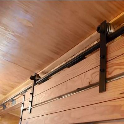 En lugar moderno Massachusetts, hay una pesada puerta corredera en pistas.  Cubre un baño húmedo que contiene una sencilla inodoro de compostaje, lavabo y ducha.  (Youtube, Relax Casetas)