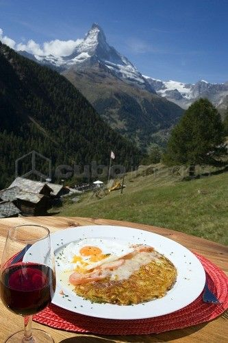 Roesti with fried eggs on a plate and a glass of red wine served in a mountain restaurant, Findeln, Matterhorn (4478 m) in background, Zermatt, Valais, Switzerland