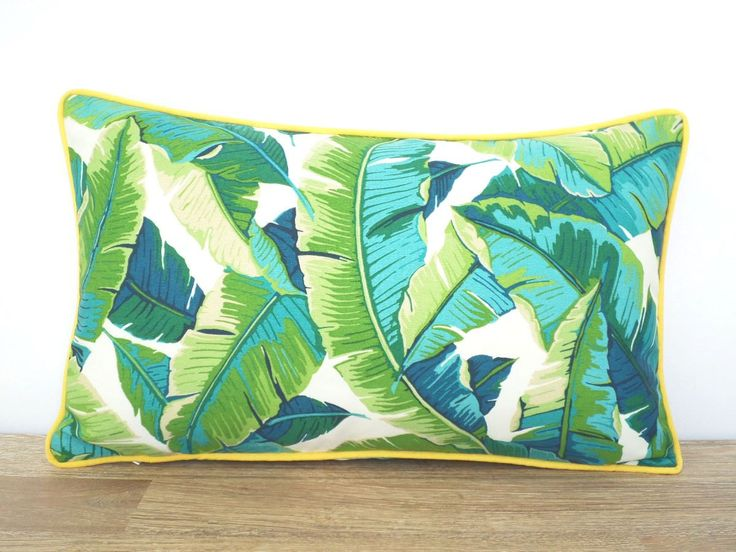This tropical lumbar pillow cover comes in an indoor/outdoor fabric from Richloom and is water and stain resistant. Colors include teal, green, turquoise and cream and the outdoor pillow goes perfect with brown outdoor furniture. Ive added a piping in bright canary yellow for some accent and pop. The inner seams are serged for durability and the invisible zipper is hidden on the bottom behind the piping . Front and back of the outdoor pillow features the same fabric .  Features of the ba...