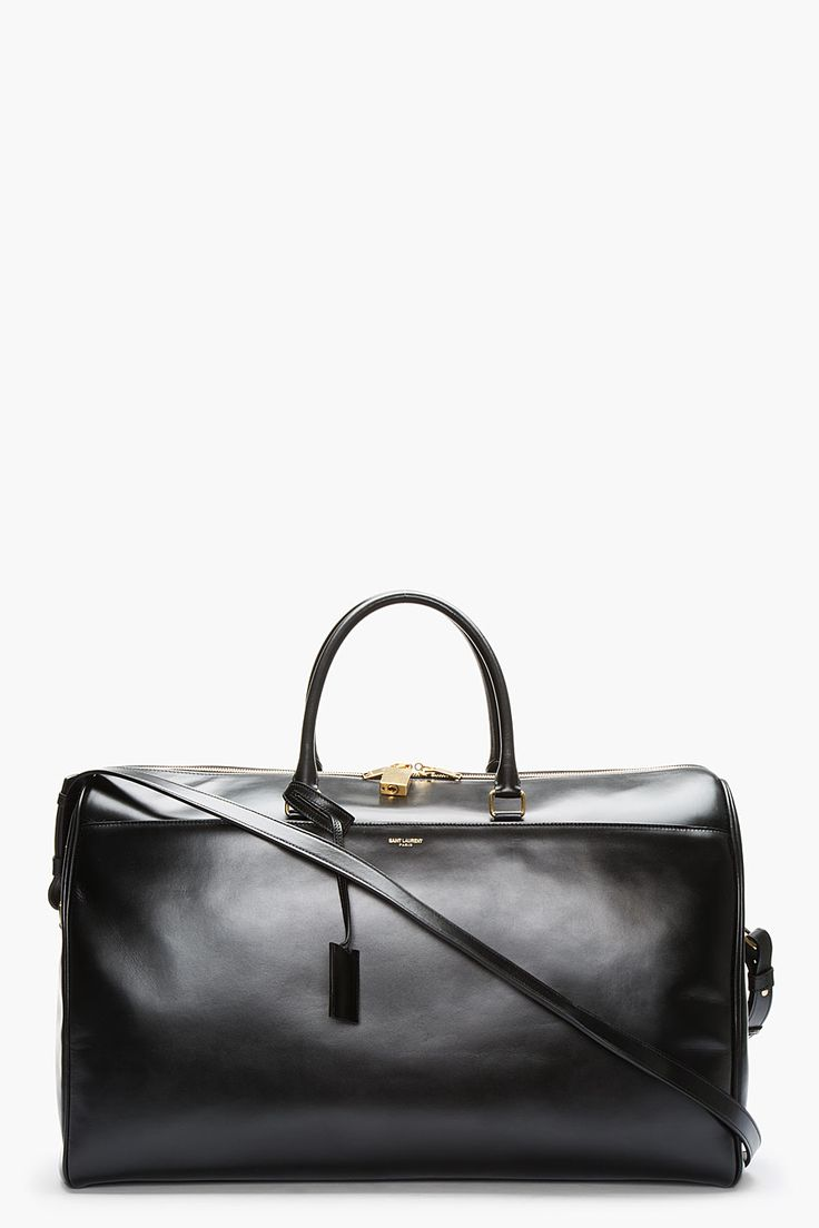 Large leather duffle bag in black. Gold tone hardware. Twin rolled leather carry handles at top with covered padlock key. Single adjustable leather shoulder strap with collar pin clasps.  http://www.zocko.com/z/JJ6SN