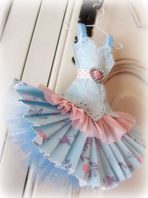 This pretty dress miniature is made from crepe, scrapbook and envelope paper.  The bodice detail is carefully stitched in pale blue cotton on an overlay of pale blue Broderie Anglaise fabric.  The pink and pale blue floral skirt features a pale pink crepe ruffle, and a ruffled undershirt skirt in pale blue sparkly tulle. It has a pale pink spotted grosgrain ribbon belt with a sparkly diamante buckle in a heart shape.