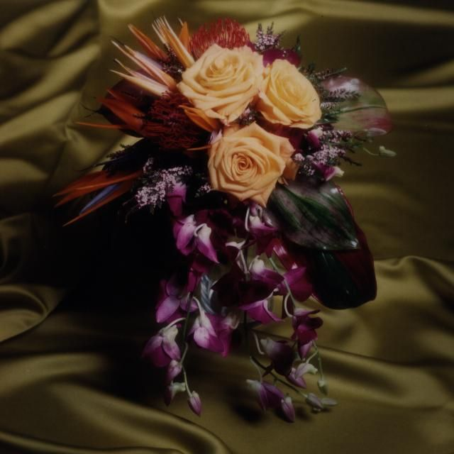 Tropical bride's bouquet. Face the camera cascade of dendrobium orchids, roses, birds of paradise, Ti leaves, etc. Photo by Judy Eliyas & Studio 925