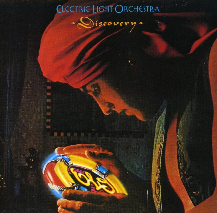 The cover of ELO Discovery is a dark background with a man in a turban, and he's holding a round colorful disc with ELO illuminated in the center.
