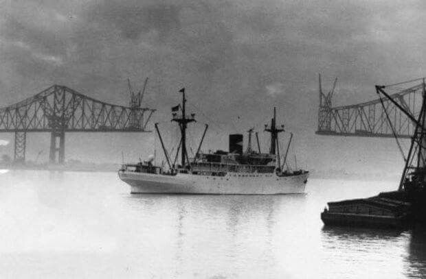 A Haunting Photo of the SS Yaque Vessel for the  United Fruit  Company  (now Chiquita) bringing in bananas from Ecuador  to New Orleans in 1957.In the background, The Mississippi River Bridge still under construction with a scheduled completion date of early 1958.