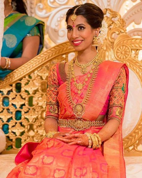 South Indian bride. Gold Indian bridal jewelry.Temple jewelry. Jhumkis. Coral pink silk kanchipuram sari.Side braid with fresh jasmine flowers. Tamil bride. Telugu bride. Kannada bride. Hindu bride. Malayalee bride.Kerala bride.South Indian wedding.