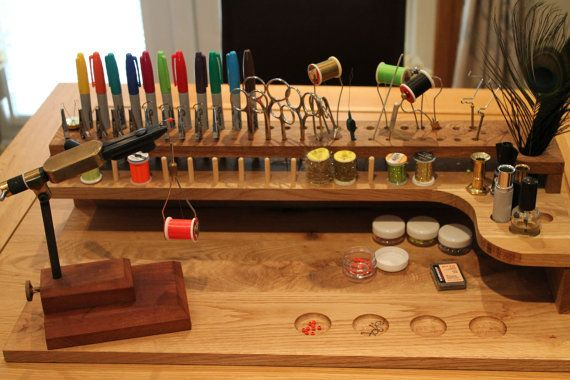 Solid Oak fly tying station, hand made for use with a pedistal tying vice. Station has capacity to hold pens, tools, spools and feathers in easy reach.  There are ten clips included to hold flies as the head cement/varnish dries. 15 pegs for spooled material 12 holes at 12mm dia, 10 at 8.5mm dia, 8 at 7mm dia and 10 at 6mm dia for holding tools. 10 holes at 5mm dia to hold the included clips. 3 recesses at 22mm dia to hold hair stackers, dubbing spinners etc. 1 recess at 32mm dia to head...