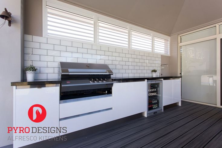 Alfresco kitchen with Eleganz perspex doors, a Ziegler and Brown BBQ and subway tiles printed onto a glass splashback