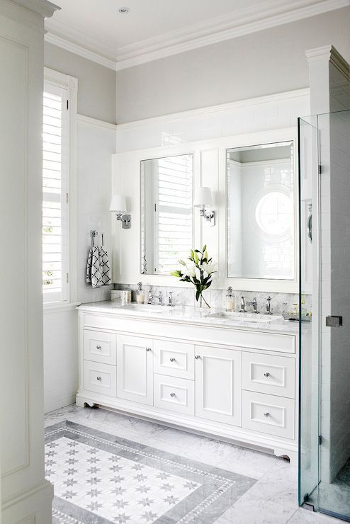 White and grey bathroom features custom double vanity paired with white marble countertop and a seamless marble backsplash under beveled medicine cabinets ensconced in white moldings atop a white subway tiled backsplash over white marble tiled floors framing a carpet of gray mosaic inset tiles.