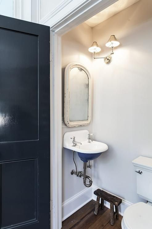 A glossy blue door opens to a tiny vintage powder room boasting a white distressed vanity mirror mounted on a white wall above a blue wall mount vintage wall sink illuminated by a nickel 2 light sconce mounted on an adjacent wall above a small reclaimed wood stool positioned on wood plank floors.