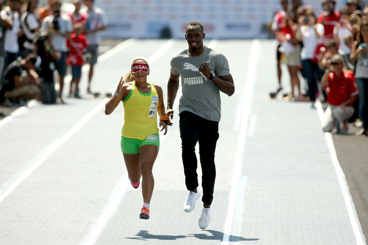Try to keep up Bolt! lol -- Terezinha Guilhermina with Usain Bolt running as her guide during an exhibition in preparation for the Mano a Mano Athletics Challenge at the Jockey Club Brasileiro in Rio de Janeiro, Brazil.