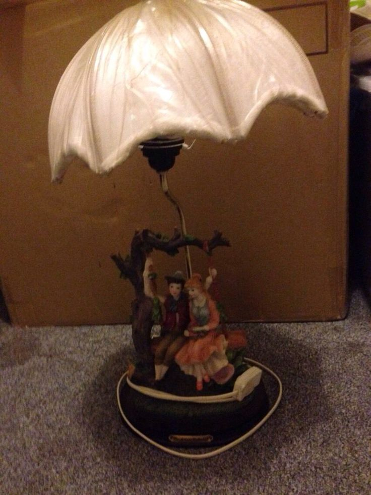 "Brand New bedside or ornamental lamp by ""The Milano Collection"" of boy and girl on swing the top shade has beaded tassels when unwrapped THAT hang down the shade NICE collectors item"