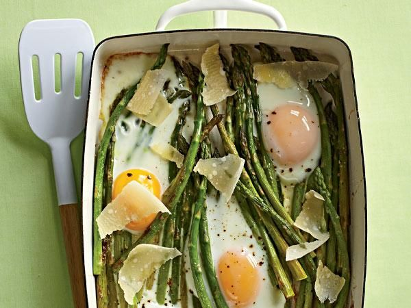 1. Spread 1 bunch asparagus in oiled dish. Bake at 425°F until crisp-tender, 15 min.  2. Crack 4 lg eggs over top and sprinkle with pepper. Bake until whites are set and yolks reach desired doneness, 10 min.  3. Top with 2 Tbsp shaved Parmesan.
