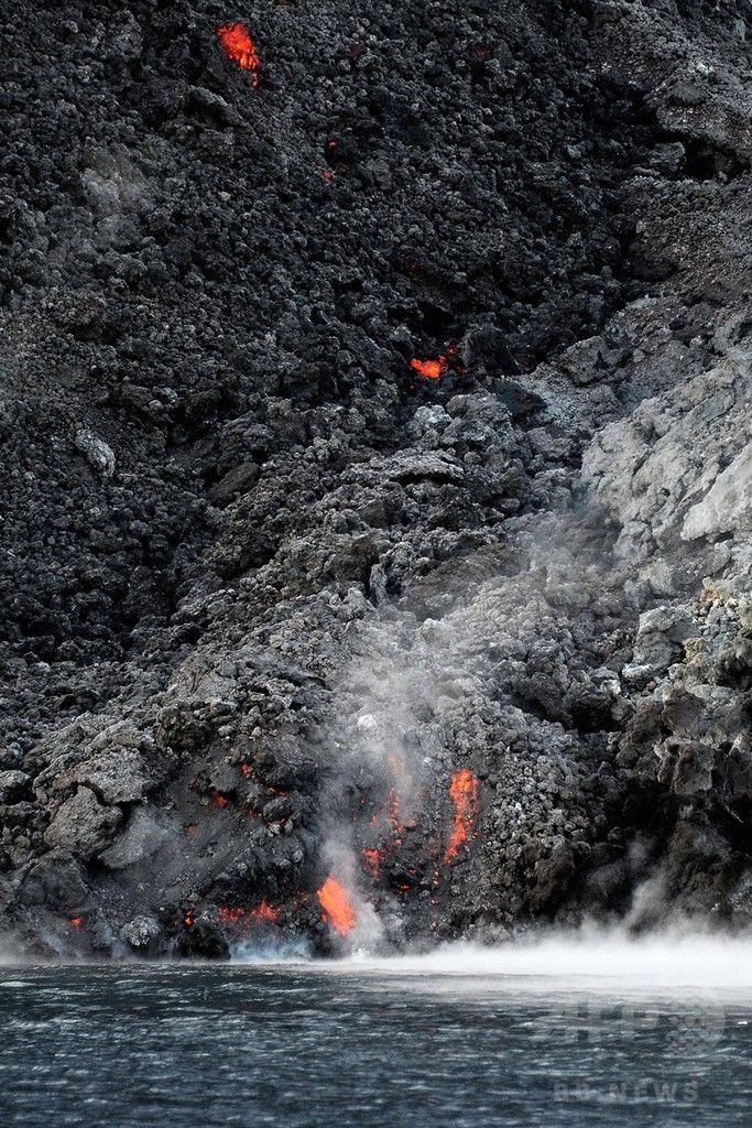 イタリア南部のシチリア(Sicily)島沖にあるストロンボリ(Stromboli)火山から噴き出し、海に流れ込む溶岩(2014年8月10日撮影)。(c)AFP/GIOVANNI ISOLINO