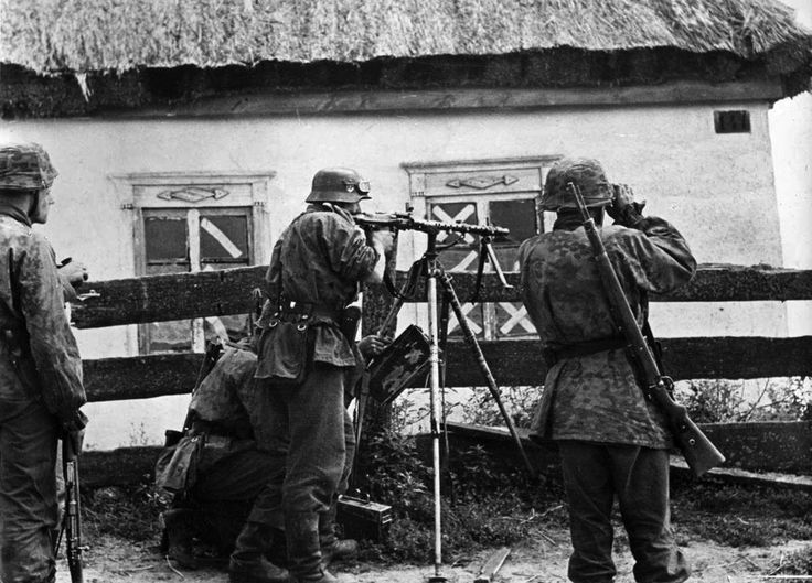 Great display of firepower from the soldiers of Leibstandarte Division along fenced area of a Ukrainian farmhouse during Operation Barbarossa in 1941. If the sniper fire is not adequate, a few bursts from the MG 34 machine gun will suppress any enemy activity.