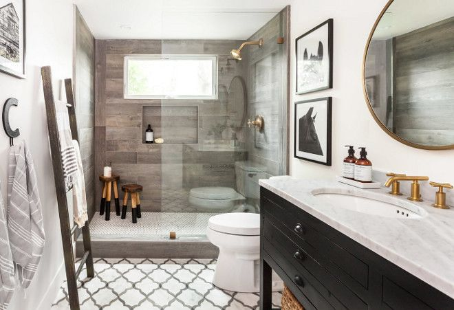 farmhouse bathroom featuring off-white walls, marble flooring, wood-like shower tile and rustic black vanity